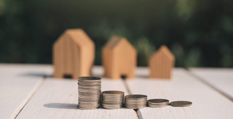Casitas de madera pequeñas con torres de monedas en frente.